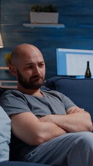 Uomo frustrato che fissa nello spazio seduto da solo sul divano sentendosi depresso