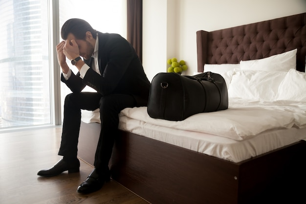 Frustrated man in suit sitting on bed besides luggage bag.