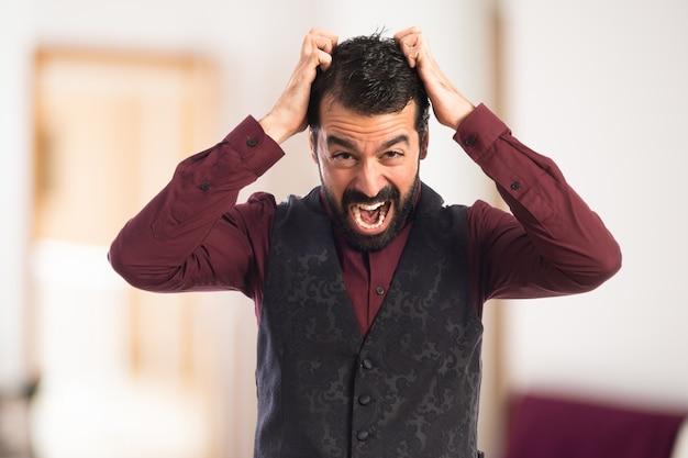 Frustrated man wearing waistcoat on unfocused background