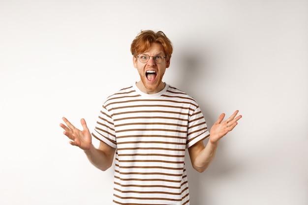 악수 하 고 카메라에 고 함, 화가 불쾌 하 게 찾고, 흰색 배경 위에 서있는 빨간 머리를 가진 좌절 된 남자.