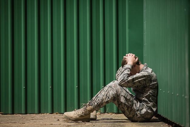 ブートキャンプで頭に手を置いて座っている欲求不満の軍兵士
