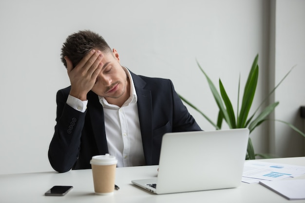 Uomo d'affari millenario frustrato che ha forte emicrania stanco dal lavoro del computer portatile