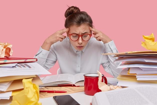 Разочарованный ботаник сосредоточен на книге, держит пальцы на висках, пытается запомнить информацию, занят перед экзаменом, волосы зачесаны в пучок
