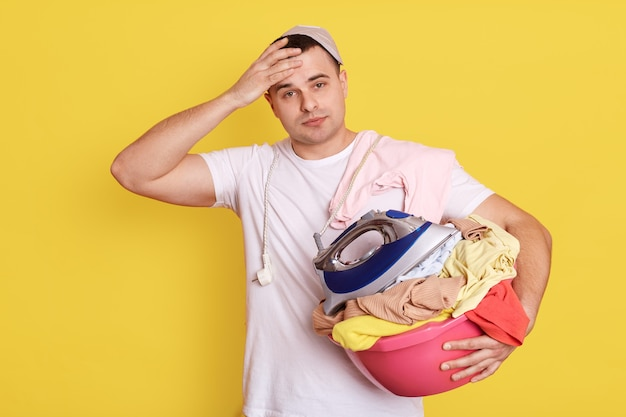 Frustrated overworked man posing with basin full of dirty clothes, having much home duties, stands with laundry basket, male wearing white t shirt isolated on yellow wall.
