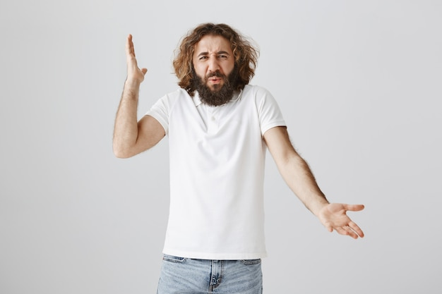 Frustrated pissed-off middle-eastern man raise hands in dismay and complaining