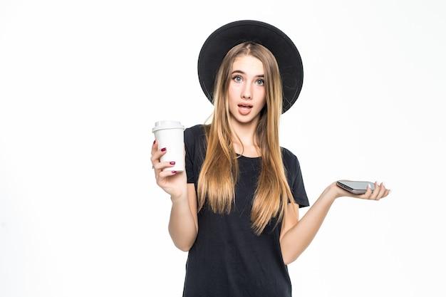 携帯電話と白い背景で隔離のコーヒーと欲求不満のかなりかわいい女の子