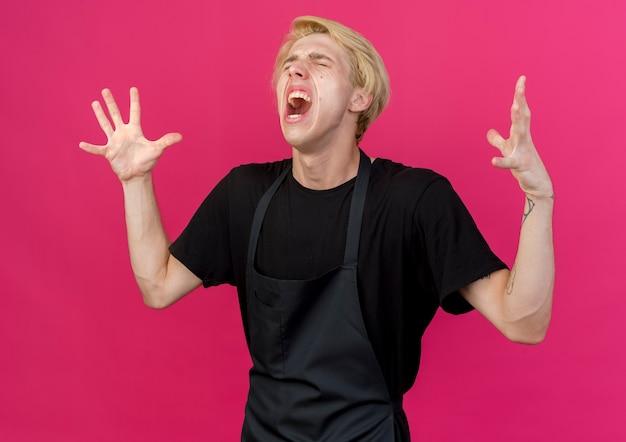 Uomo di barbiere professionista frustrato in grembiule che grida con espressione aggressiva con le braccia alzate pazzo pazzo