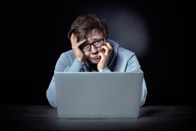 眼鏡をかけた欲求不満のプログラマーはラップトップに座って、失望、失敗の概念でカメラを見ています