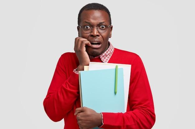 좌절 된 의아해 어두운 피부의 남성 학생은 불쾌한 표정으로 보이고 펜으로 교과서를 보유하고 있습니다.