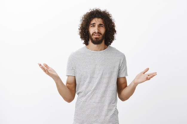 Frustrated questioned handsome man with beard and curly hair, spread hands cluelessly