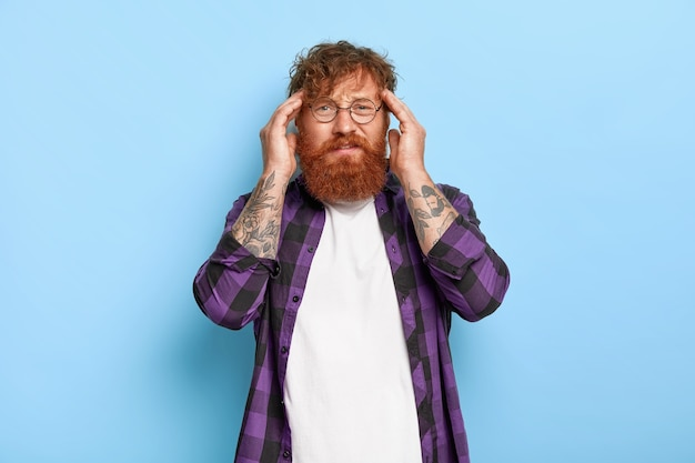 Un uomo frustrato dai capelli rossi con una folta barba tocca le tempie, soffre di un'enorme emicrania, ha bisogno di antidolorifici