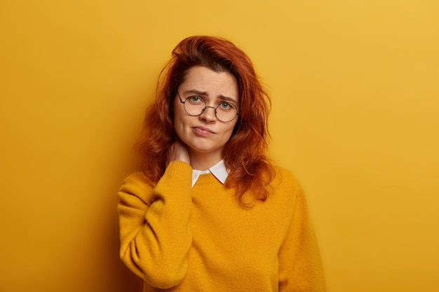 Frustrated red haired woman has strong pain in neck after working long time at computer, looks sadly at camera, suffers from osteohondrosis, has gloomy expression