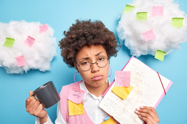 Разочарованный грустный афроамериканский студент устал выражение лица, чувствует себя сонным после подготовки к экзамену целый день в окружении наклеенных наклеек делает пометки на листах, чтобы запомнить информацию пьет кофе