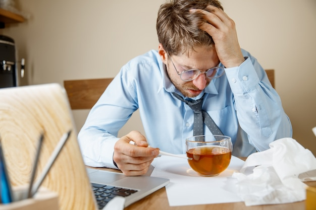 Frustrated sad unhappy sick young man massaging his head while sitting at his working place in office
