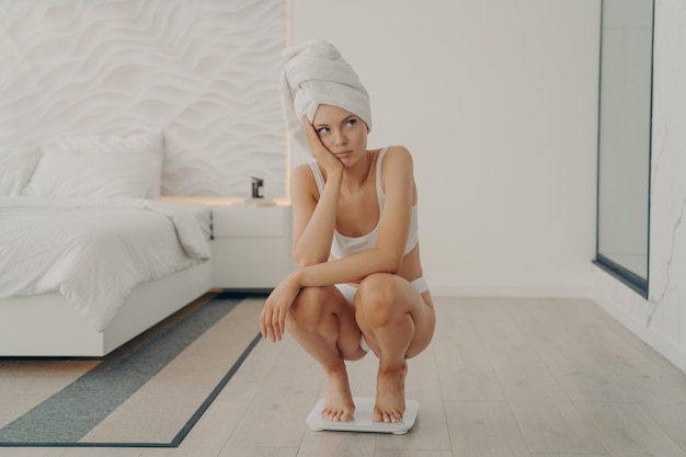 Frustrated sad young european girl squats on scales in bedroom after shower, gaining and not losing excess weight, having hard time to slim. weight loss problem concept