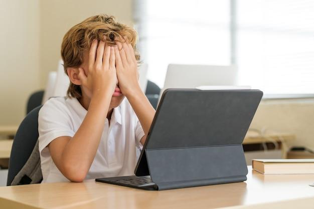 Разочарованный школьник закрыл лицо за столом в классе