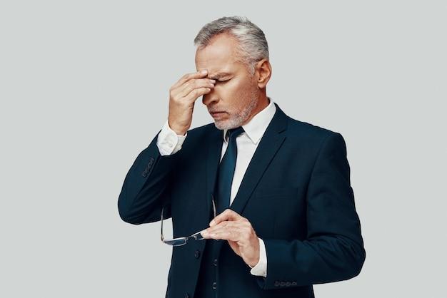 Разочарованный старший мужчина в полном костюме страдает от головной боли, стоя на сером фоне