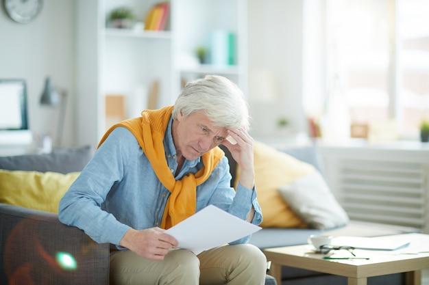 Разочарованный старший мужчина, глядя на документ
