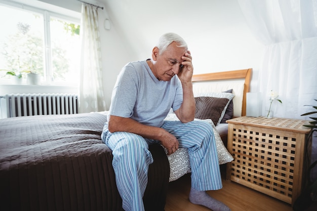 Разочарованный старший мужчина сидит на кровати