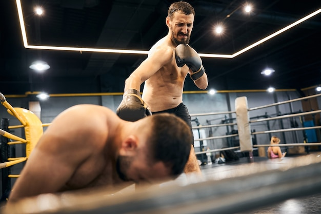 Frustrated shirtless athletic man attacking his boxing partner lying at the ring corner with his fist
