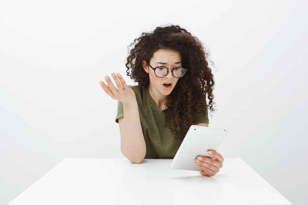 Frustrated shocked attractive curly-haired creative designer in black trendy eyewear, sitting at table, raising hand cluelessly and staring confused at digital tablet