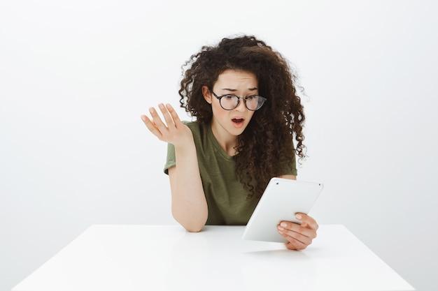 Разочарованный и шокированный привлекательный кудрявый креативный дизайнер в модных черных очках сидит за столом, невежественно поднимает руку и смущенно смотрит на цифровой планшет
