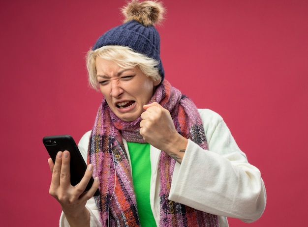 ピンクの背景の上に立っているスマートフォンを握りこぶしを握って気分が悪い暖かいスカーフと帽子の短い髪の欲求不満の病気の不健康な女性