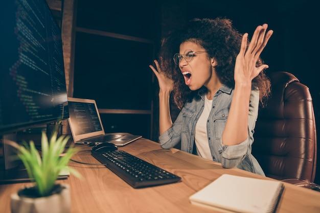 欲求不満のストレスを受けたアフリカ系アメリカ人の女の子がコンピューター画面を叫ぶ