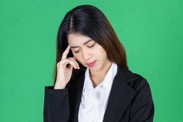 顔に手でイライラした重点を置かれた若いアジア女性実業家
