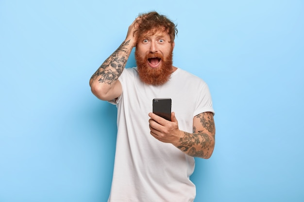 Frustrated stressful ginger hipster keeps hand on head, looks with worried facial expression, opens mouth, holds modern cellular, feels fear because of making mistake, did something wrong with app