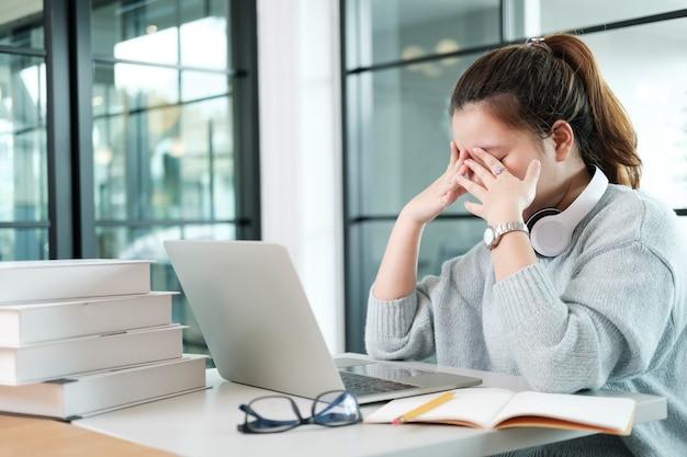 평상복을 입은 좌절한 학생은 눈을 감고 메모장과 노트북으로 테이블에 앉아 머리를 만지는 동안 문제를 해결하려고 노력합니다.