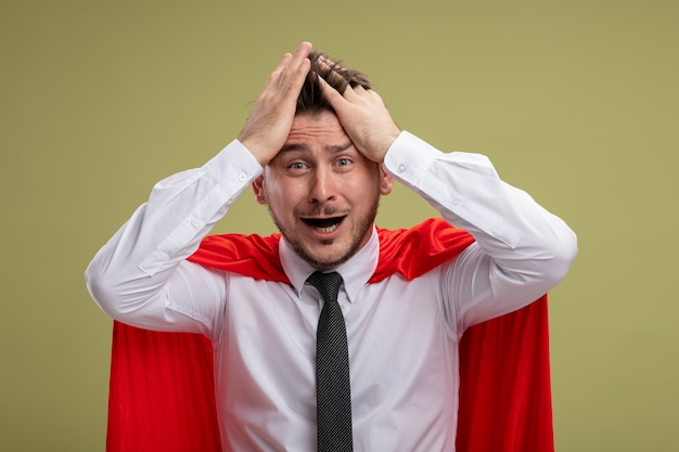Frustrated super hero businessman in red cape shouting and yelling pulling his hair going wild standing over green background