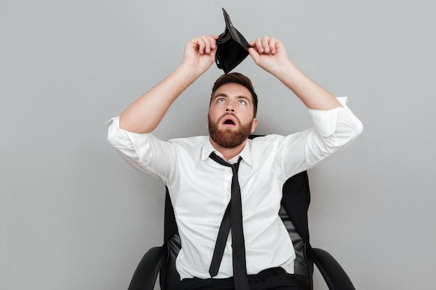 Uomo barbuto sorpreso frustrato in camicia bianca che mostra portafoglio vuoto