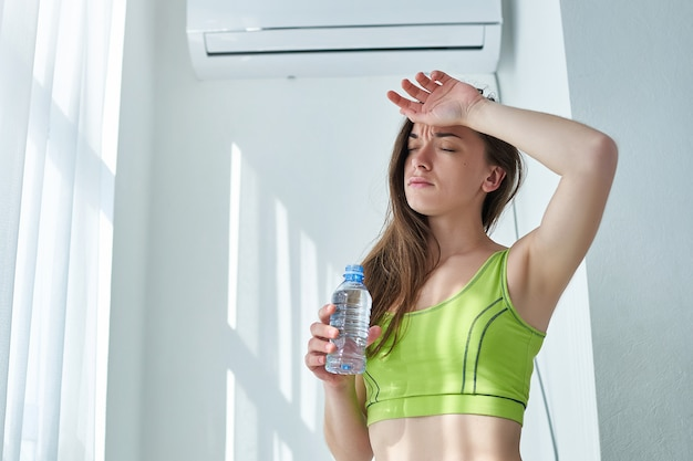 Frustrated sweating woman suffering from heat, thirst and hot weather cools down with air conditioning and cold refreshing water bottle.