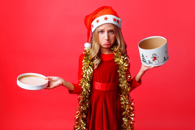 Frustrated teenage girl in santa hat and tinsel on neck opening box,