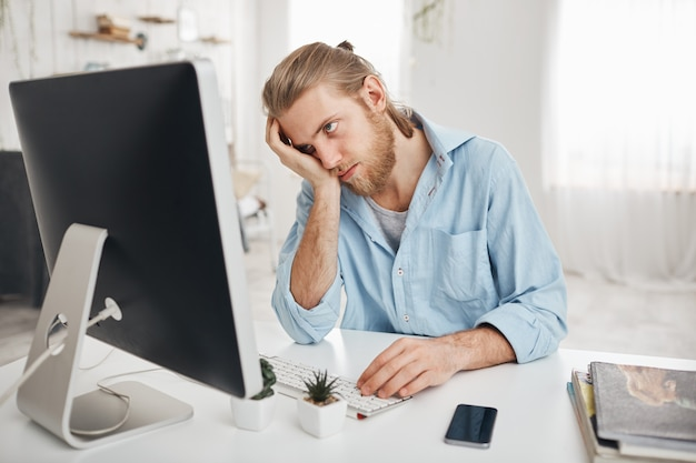 Frustrated tired bearded caucasian employee touching his head, feeling absolutely exhausted because of overwork, calculating accounts, sitting in front of computer screen. deadline and overwork