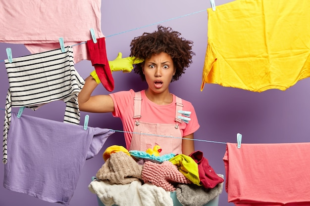 Frustrated tired housewife fed up with home routine and domestic work, makes suicide gesture, shoots at temple with finger, stands near pile of laundry, hangs wet clean clothes on clothesline