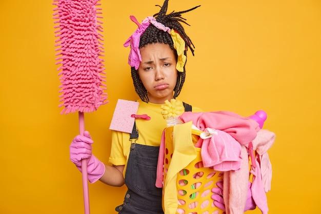 La casalinga stanca e frustrata tiene la scopa e il cesto della biancheria si sente esausta di fare le pulizie a casa