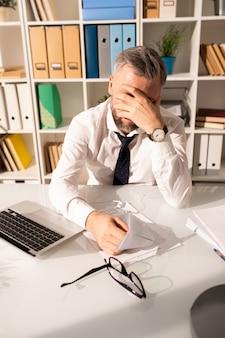 Разочарованный усталый человек, работающий с бумагами в офисе