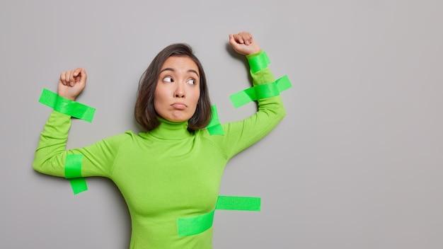 La donna asiatica infelice frustrata in dolcevita verde plastificato al muro grigio tiene le braccia alzate ha l'espressione del viso scontenta che viene catturata isolata sul muro grigio