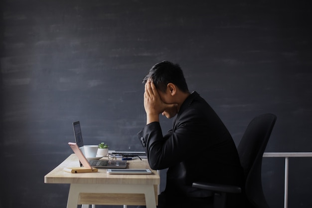 Frustrated and unhappy businessman in suit sitting on office desk with hand on head