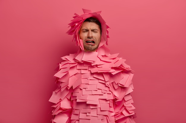 L'uomo infelice frustrato piange di disperazione, esprime emozioni negative, indossa note appiccicose intorno a tutto il corpo e alla testa, posa al chiuso contro il muro rosa, ha un'espressione abbattuta