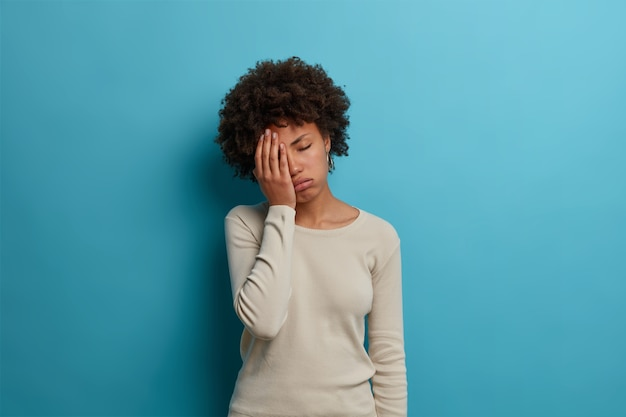 좌절 한 불행한 피곤한 젊은 여성이 손바닥을 만들고, 눈을 감고 피곤함으로 한숨을 쉬고, 흰색 점퍼를 착용하고, 파란색 벽에 포즈를 취하고, 성가신 일에 괴로워하고, 피곤함을 느낍니다.