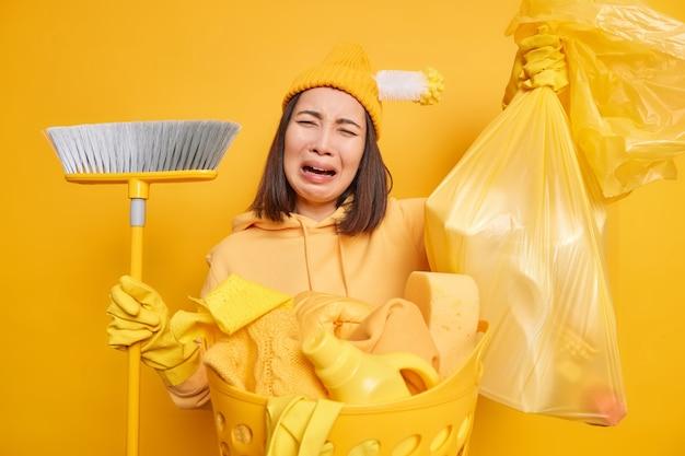 欲求不満の不幸な若いアジアの女性が絶望から叫び、家事をするのに疲れを感じて散らかった部屋にゴミを集める忙しい洗濯は黄色の背景に孤立した否定的な感情を表現します