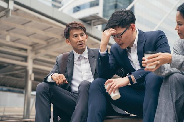 悪い仕事の結果と失望した欲求不満の動揺したアジアのビジネスチーム