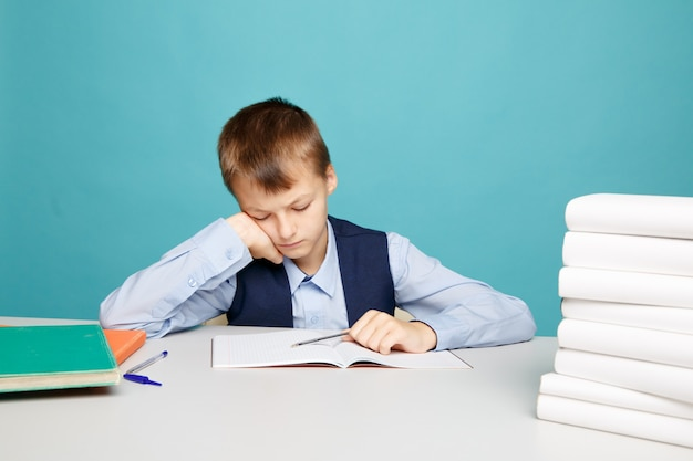Frustrated upset boy at school sitting at the desk and dotng classwork.