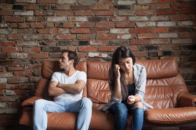 Frustrated upset couple after quarrel sitting on sofa at home