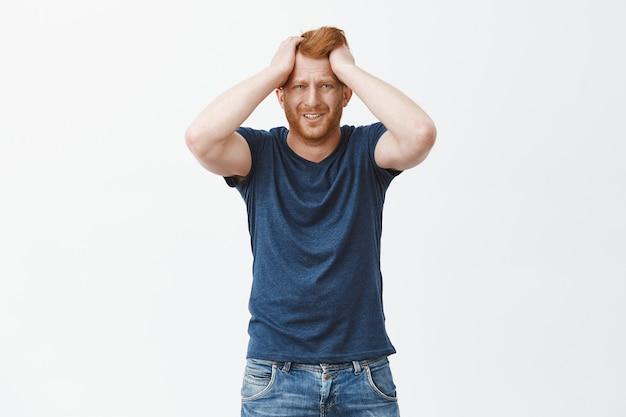 Разочарованный, расстроенный рыжий европейский мужчина в беде, держится за голову, хмурится и морщится от печали и горя