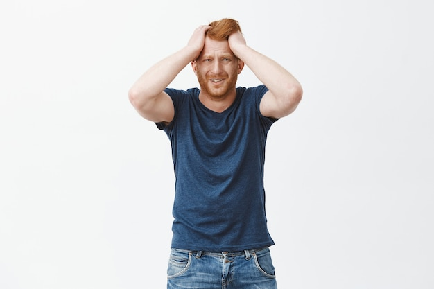 Frustrated upset redhead euroepan man in trouble, holding hands on head, frowning and grimacing from sadness and grief