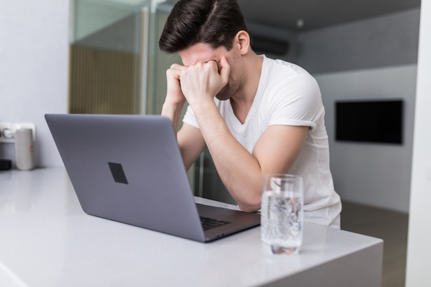 Frustrated with problems young business man working on laptop at home